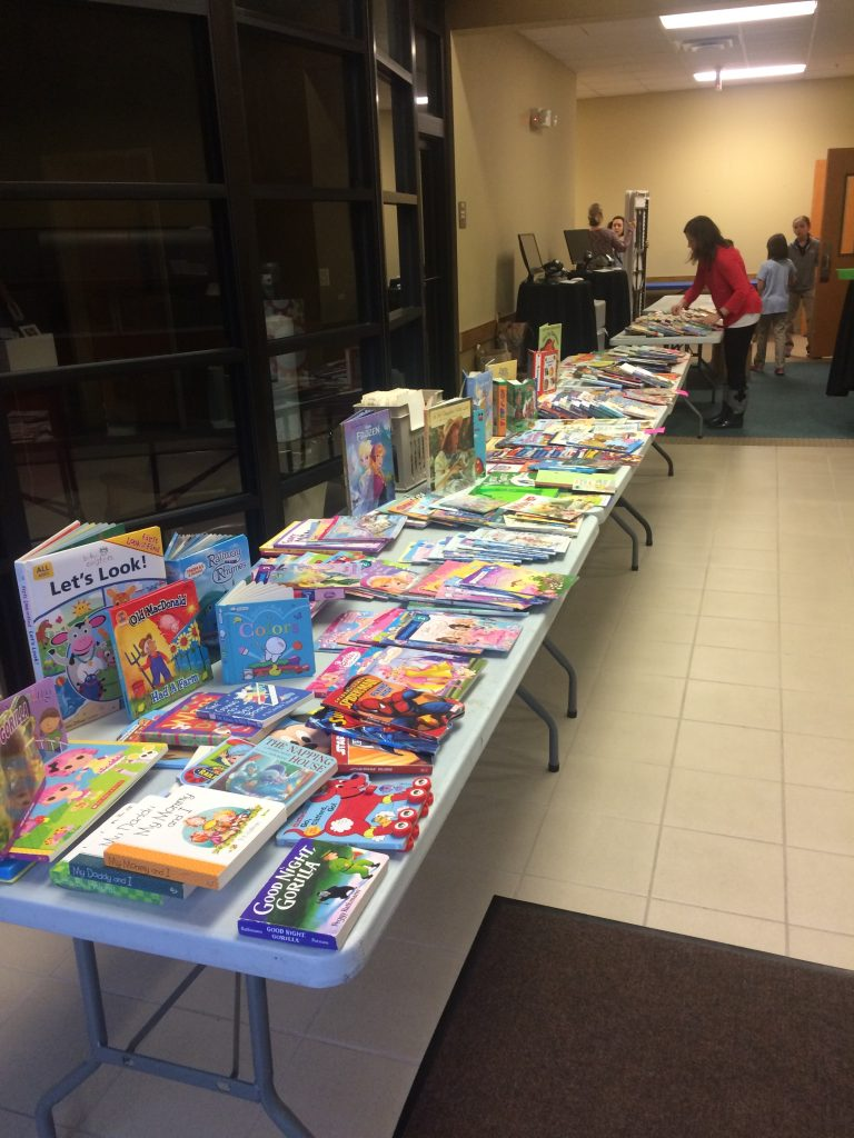 At Hope Academy, in a hallway, there are long white tables completely covered with children's books. There is a woman in a red shirt setting up books, while two woman are chatting while they set up a table. Near the back are two children.