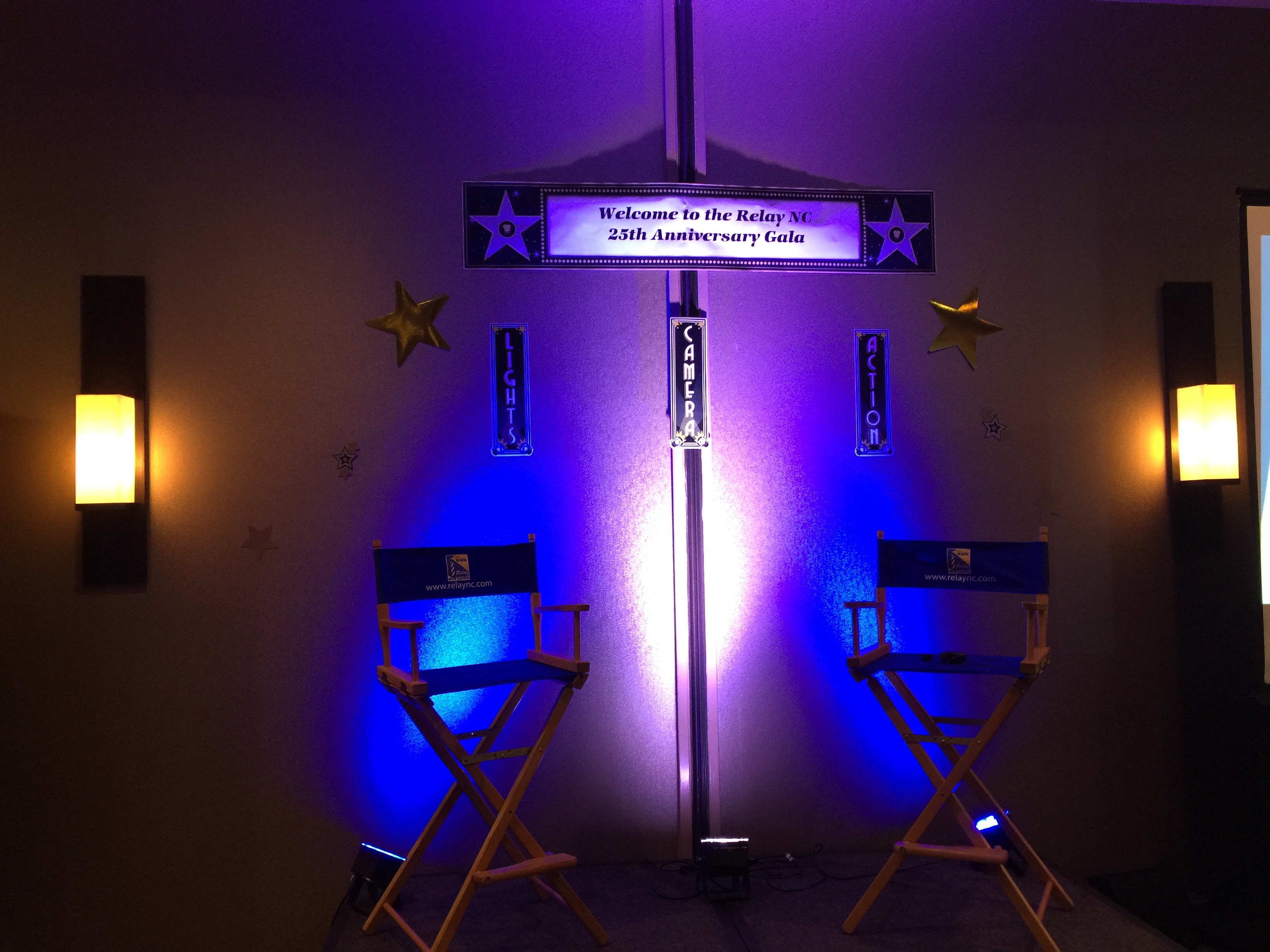 """In a dark room, on a stage, there are two director's chairs on either end with blue lights illustrating them. Above the platform is a sign that says """"Welcome to Relay NC 25th Anniversary Gala!"""" with smaller signs below that proclaiming """"Lights!"""", """"Cameras!"""", and """"Actions."""" There are also two golden stars on either side."""
