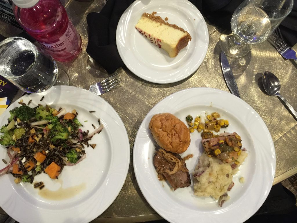 There are two dinner plates in the lower part of the image with Mediterranean Salad on the left plate, and two different meats, mashed potatoes, and some vegatables on the right plate. In the upper middle there is a dessert plate with a slice of New York Cheese Cake with raspberries toppings. There is also a pink water bottle and a water glass.