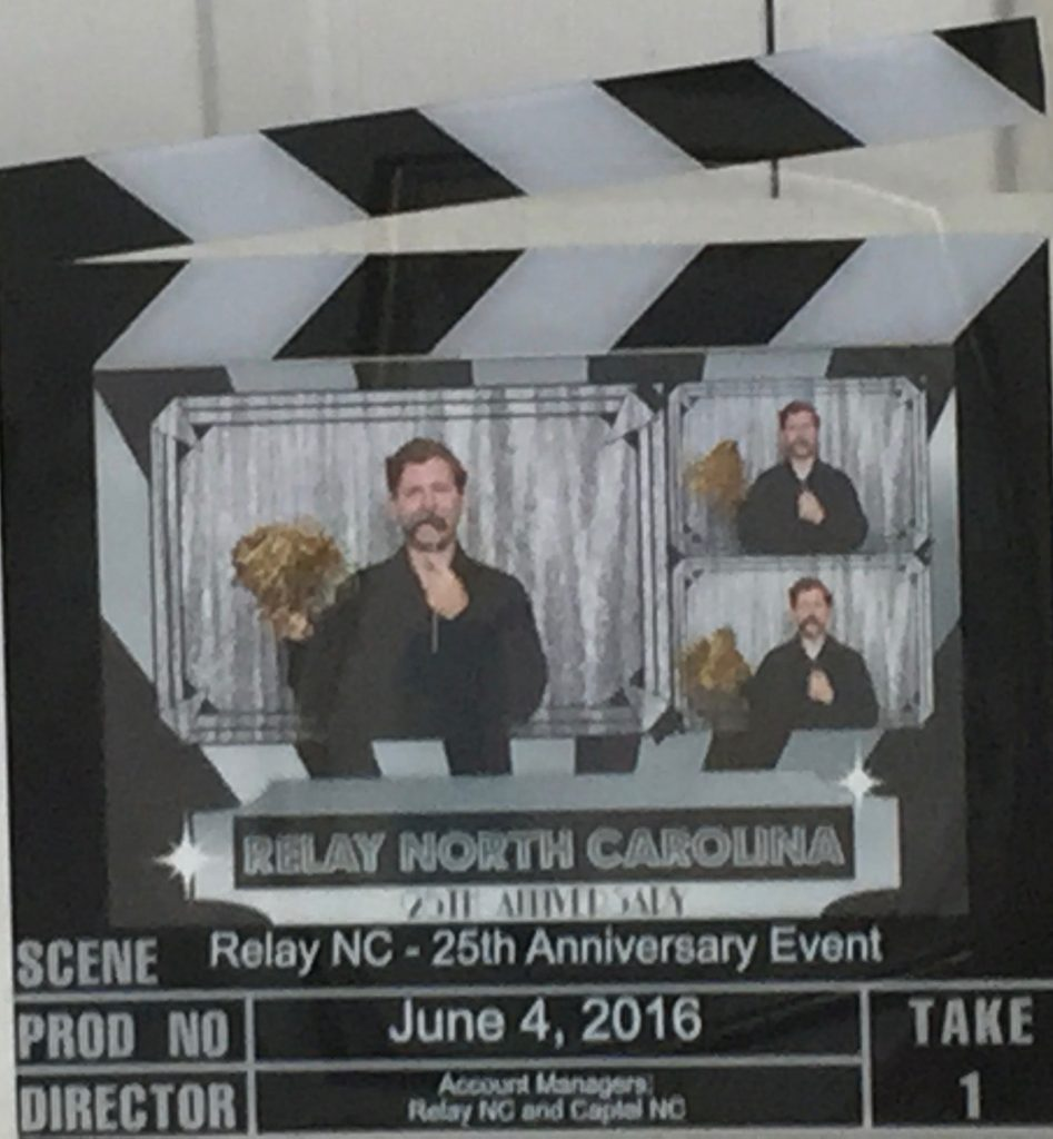 """Picture frame that looks like a movie take indicator with three images of a man (Patrick) with a silver mustache that he is holding on a stick in his left hand and in is right hand is a gold Pom Pom. He is wearing a black button down shirt and is standing in front of a silver background. The fame says on the bottom Scene: """"Relay NC 25th Anniversary Event"""" PROD NO: """"June 4, 2016"""" Director: """"Account Managers: Relay NC and Capital NC"""" And on the bottom right of the frame says """"Take 1"""""""
